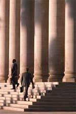 Businessmen standing outside building with pillars